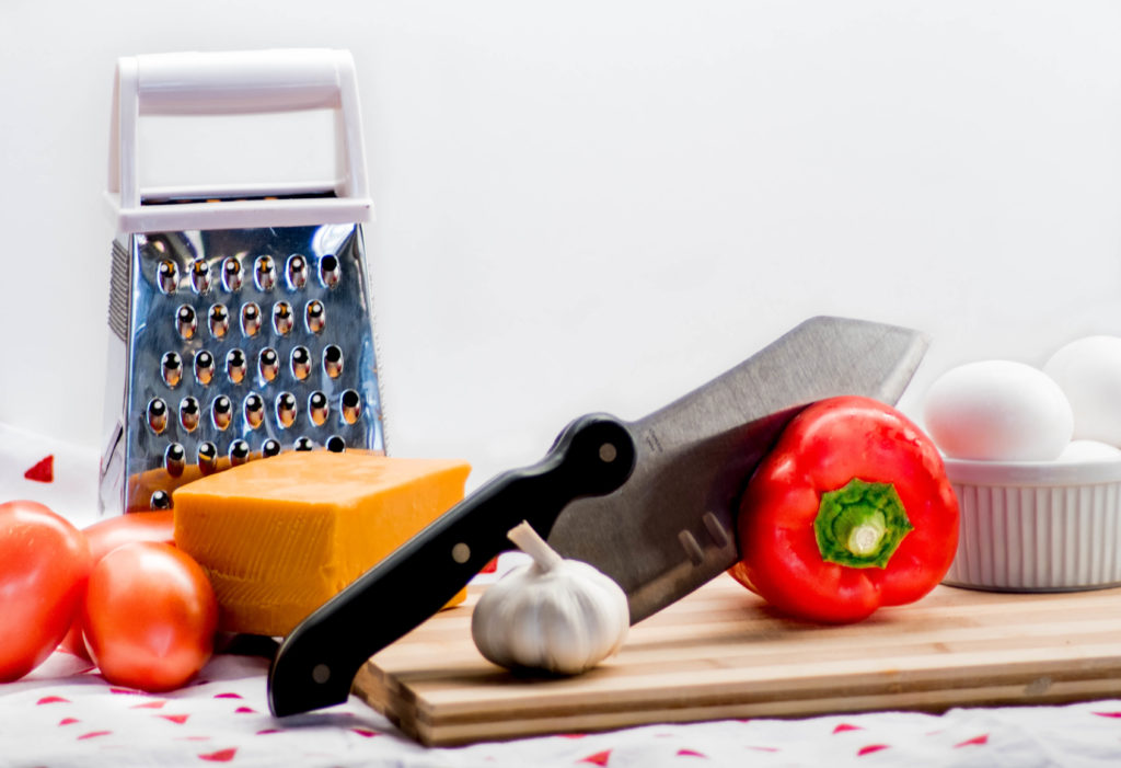 Photo with vegetables, cheese, eggs, a knife and cheese grater