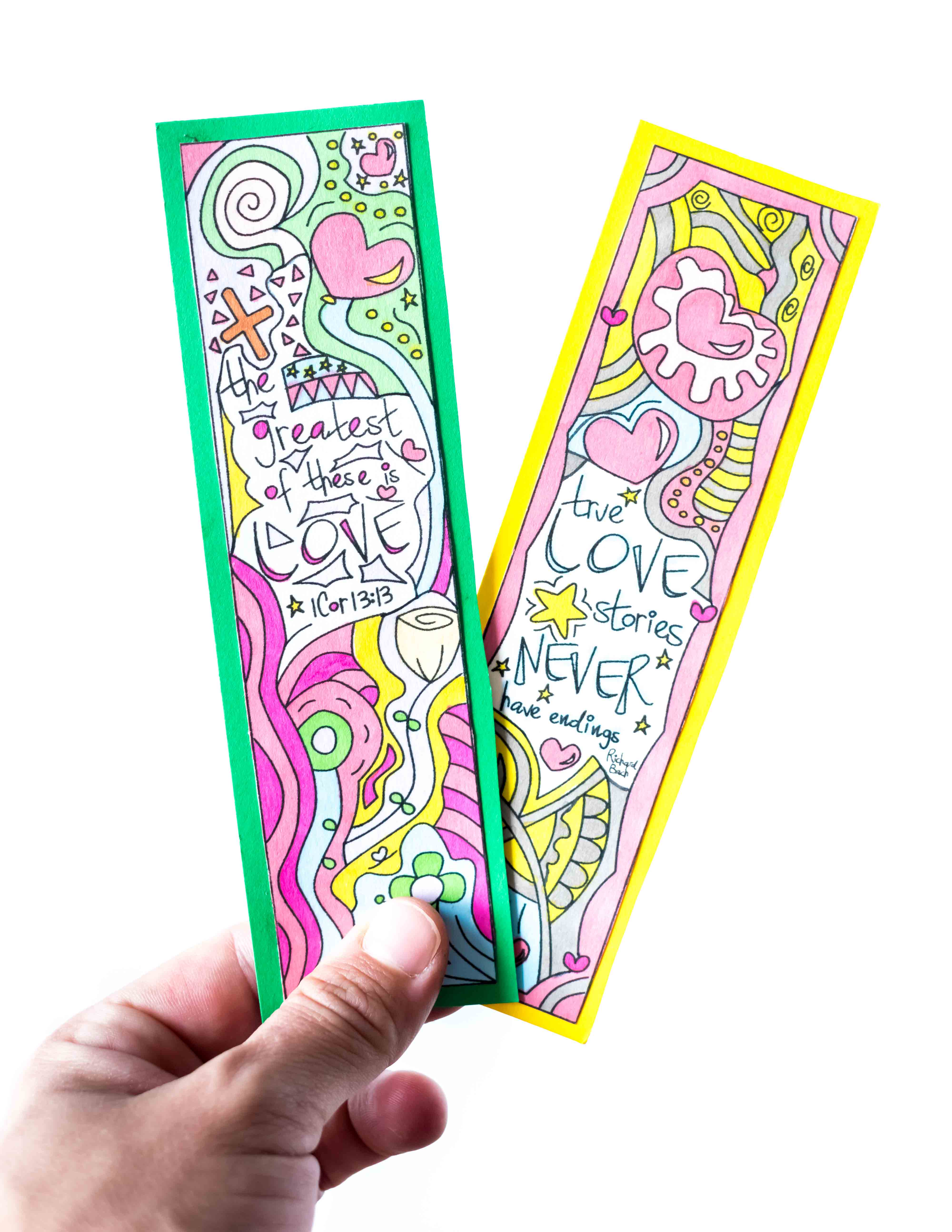 Two Valentine's Day Bookmarks being held in a white background