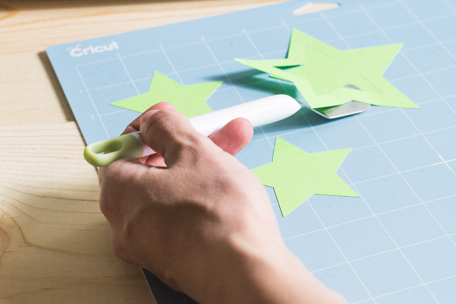 Cardstock being lifted up by the Cricut Spatula on the Blu - LightGrip Mat