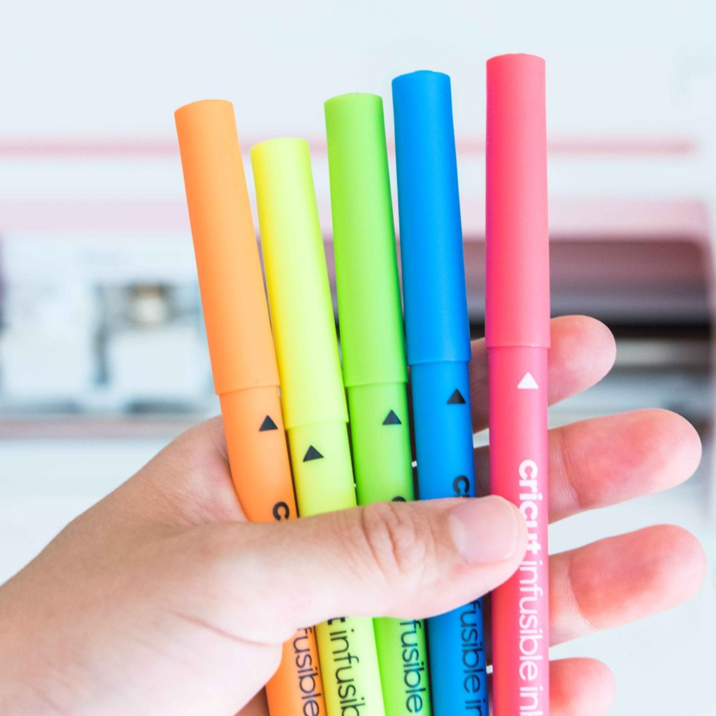Holding Cricut Infusible Ink Neon Pens