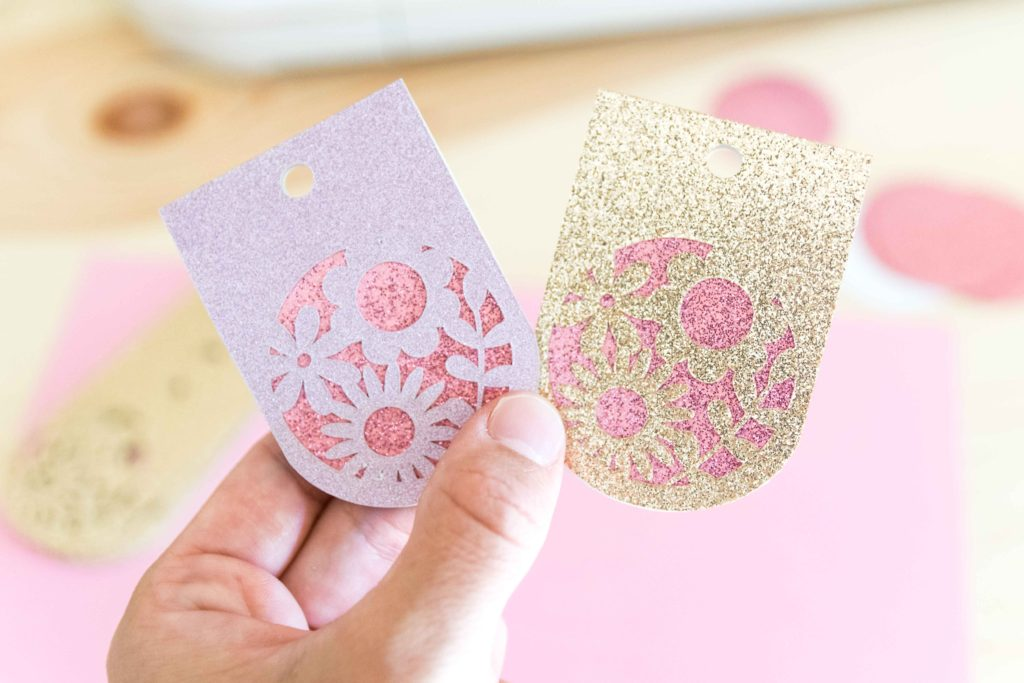 holding fancy gift tags made with Cricut Maker