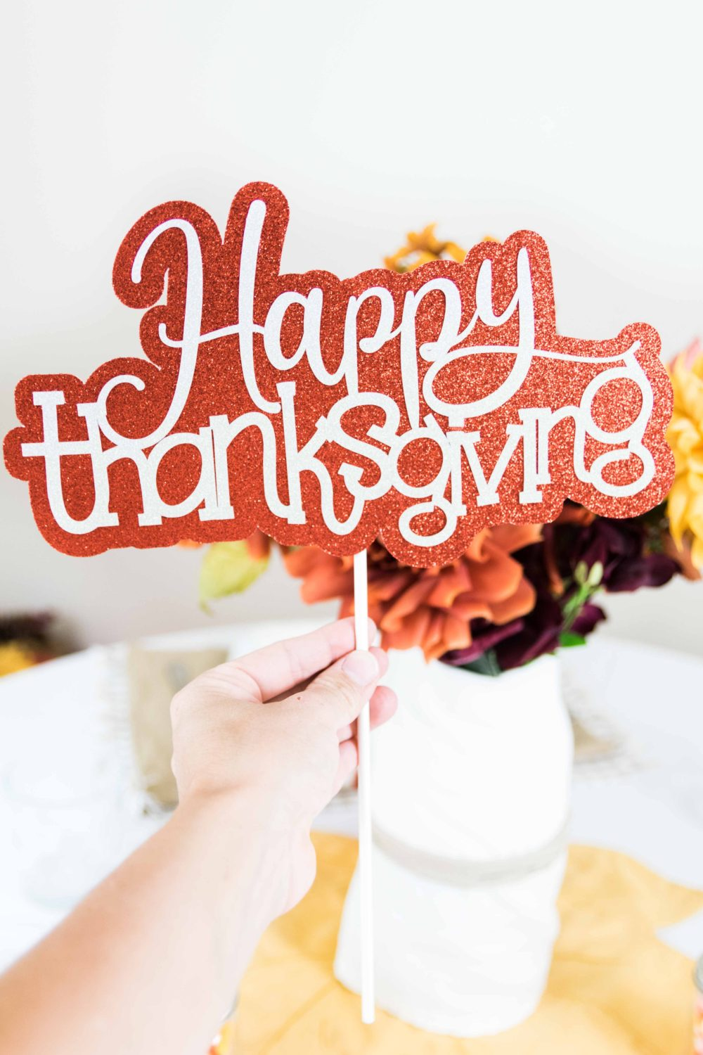 holding a happy thanksgiving cake topper