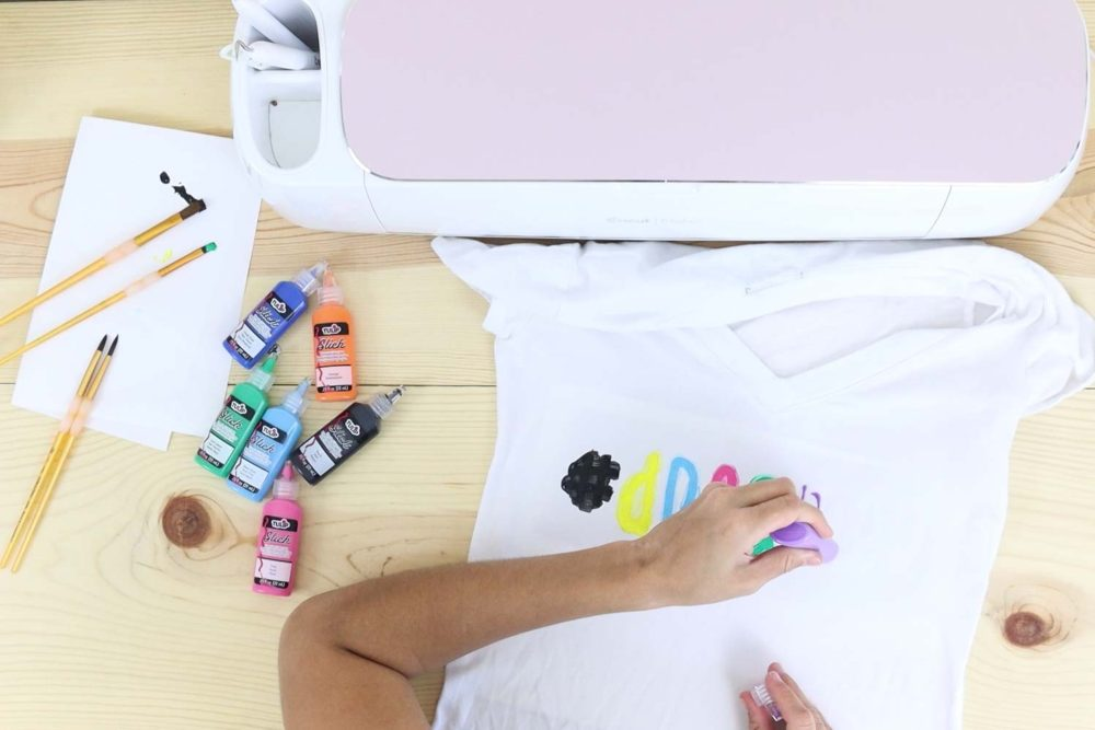Painting a t-shirt with different colors using the freezer paper stencil method.