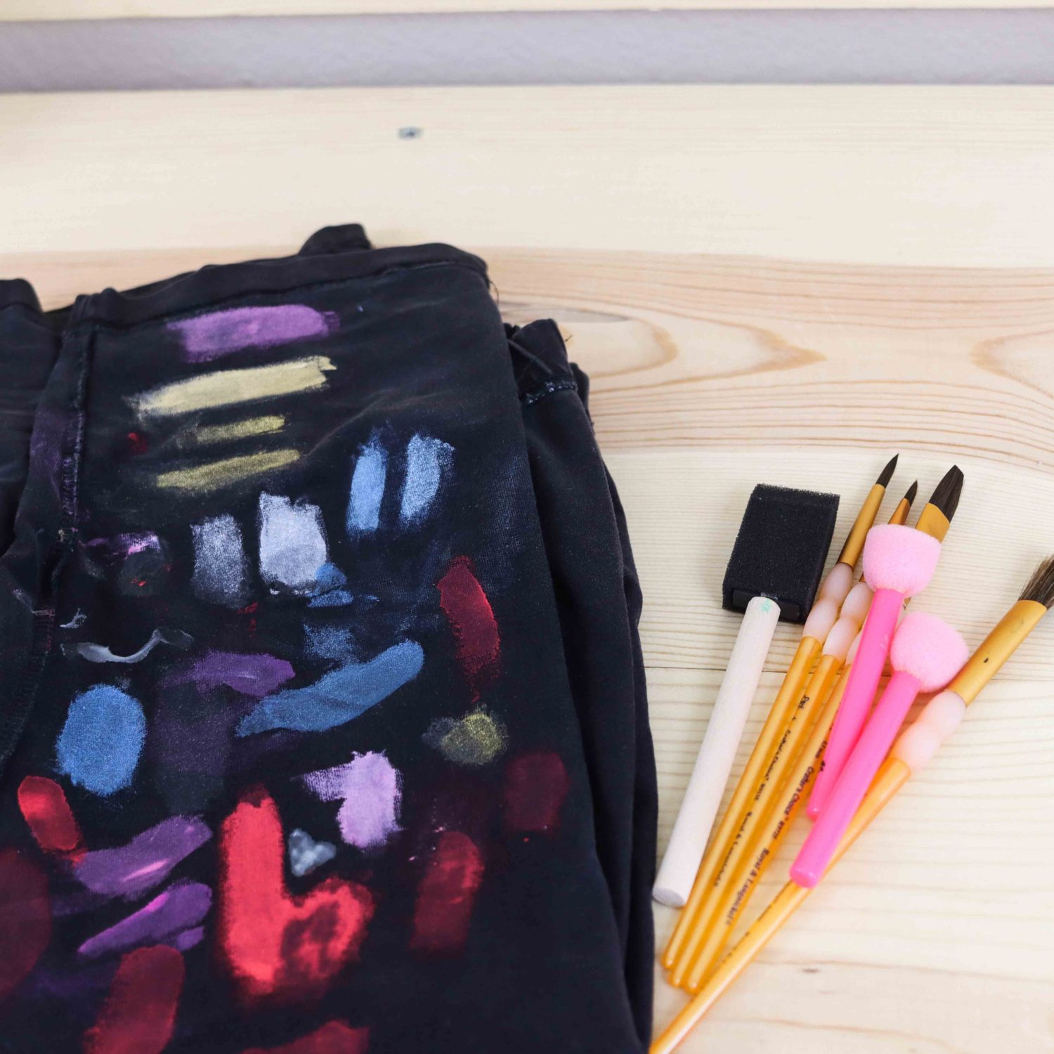 black fabric with multiple strokes of different types of fabric paint to see the pigment