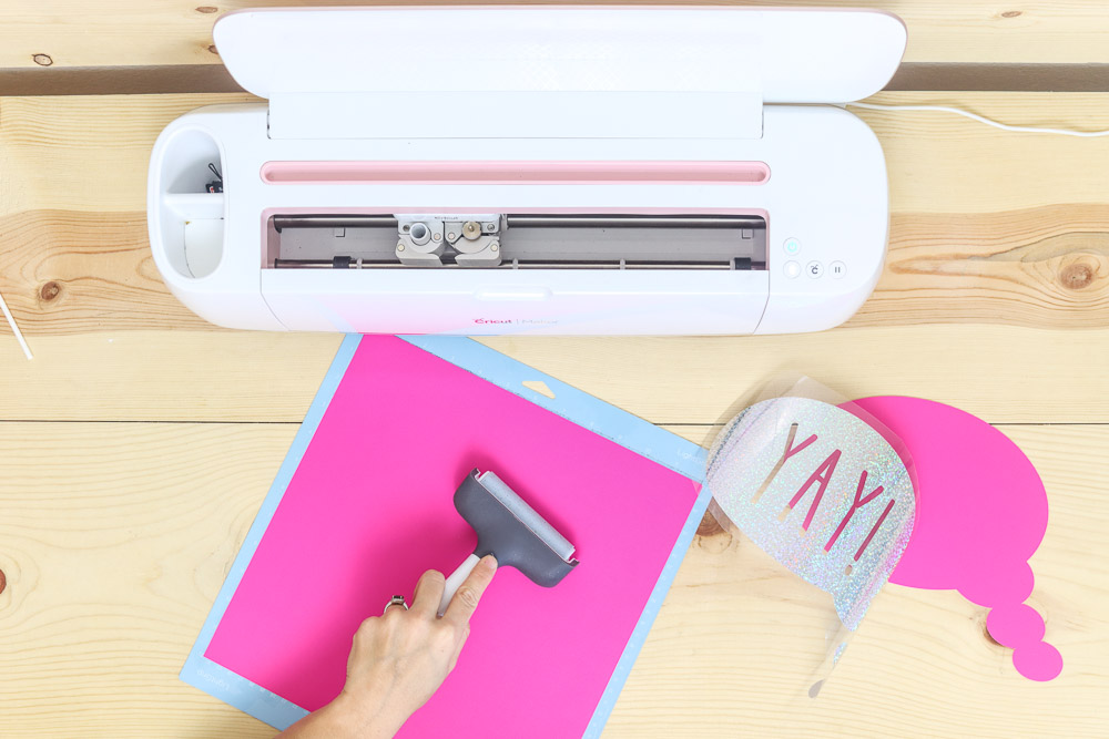 using the brayer to adhere light cardstock to the Cricut mat