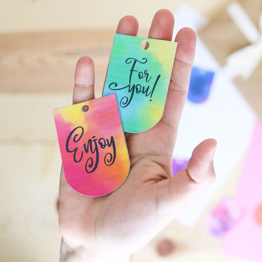 """Holding watercolor gift tags that say """"for you"""" and """"enjoy"""""""