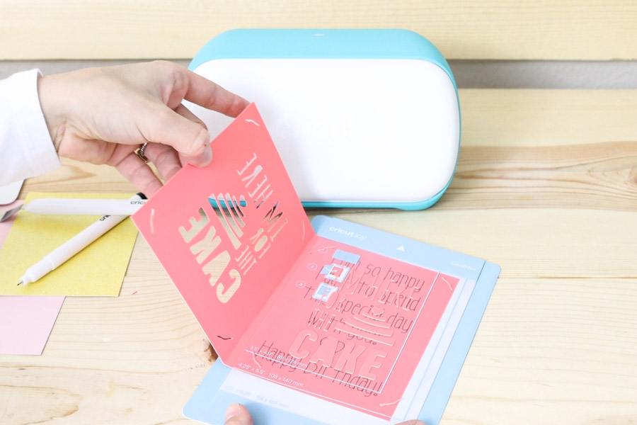 removing card from card mat after cutting and writing.