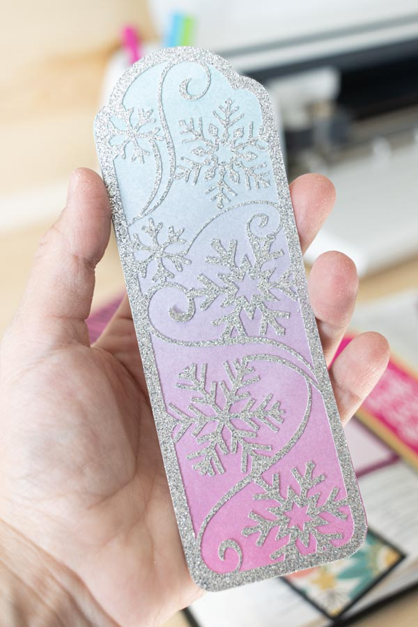 Holding a winter bookmark made with Cricut