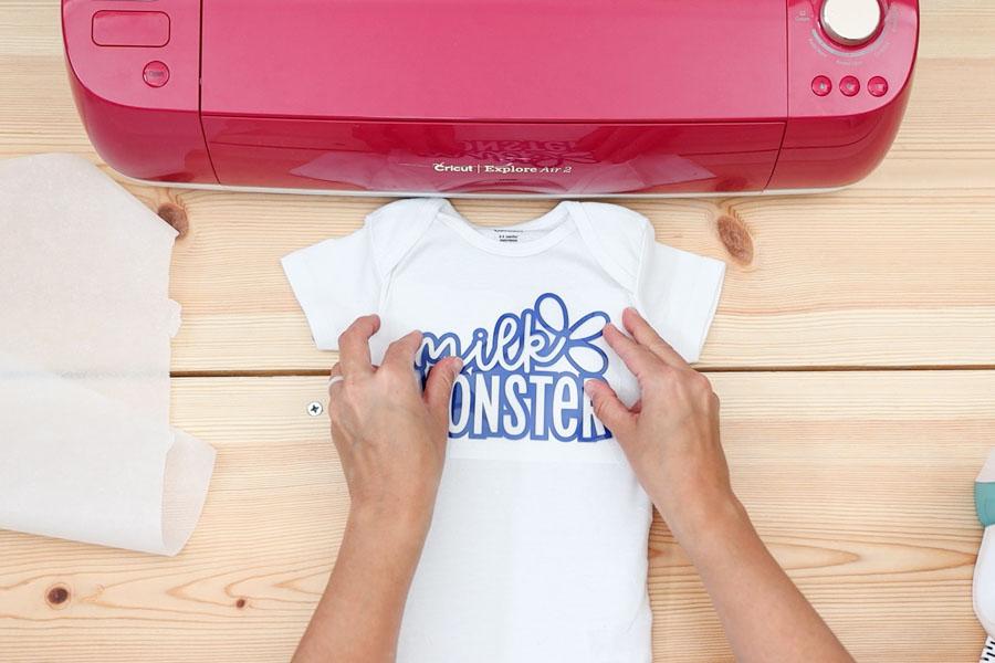 placing iron on design (milk monster) on onesie