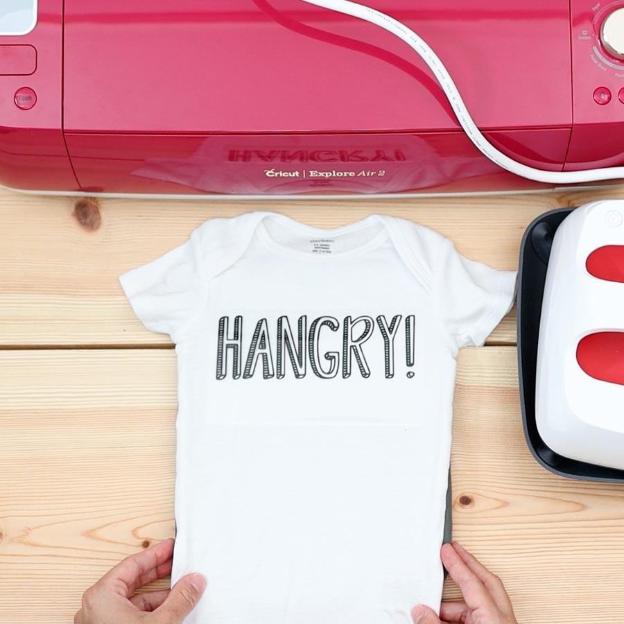 placing hangry design on baby onesie