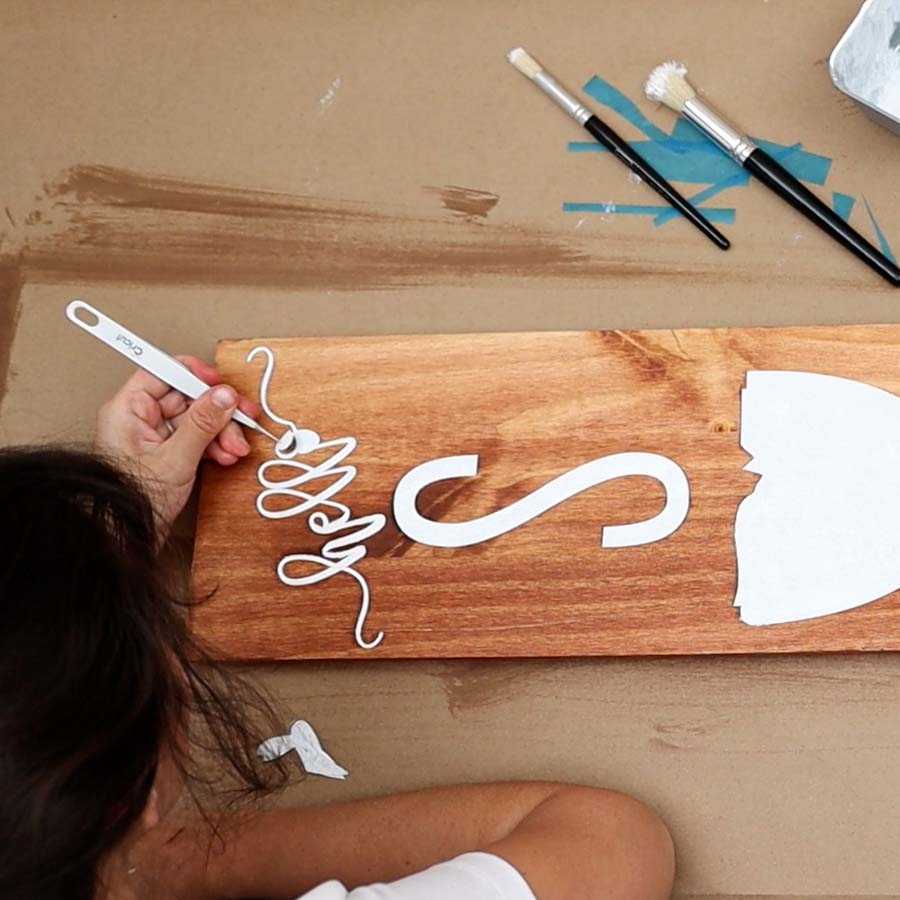 using tweezers to remove stencil vinyl from wood