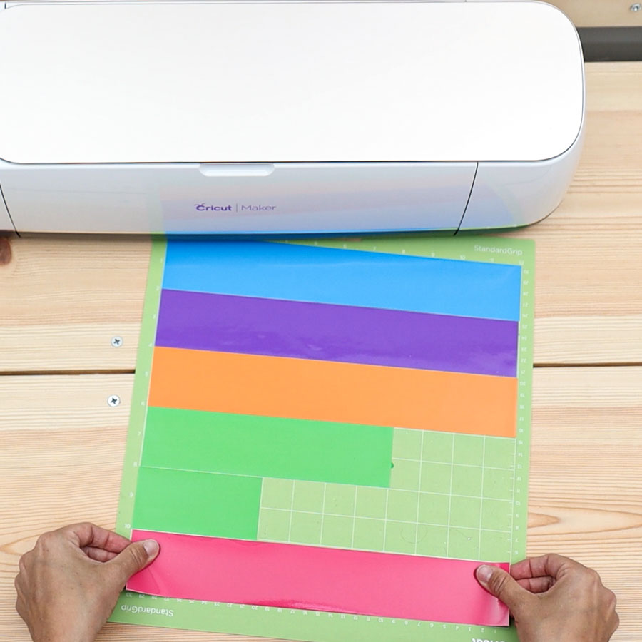 placing adhesive vinyl on mat to cut labels