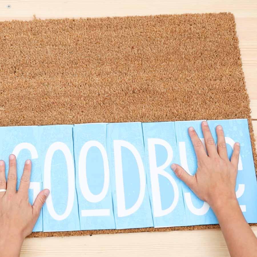 placing stencil vinyl on doormat