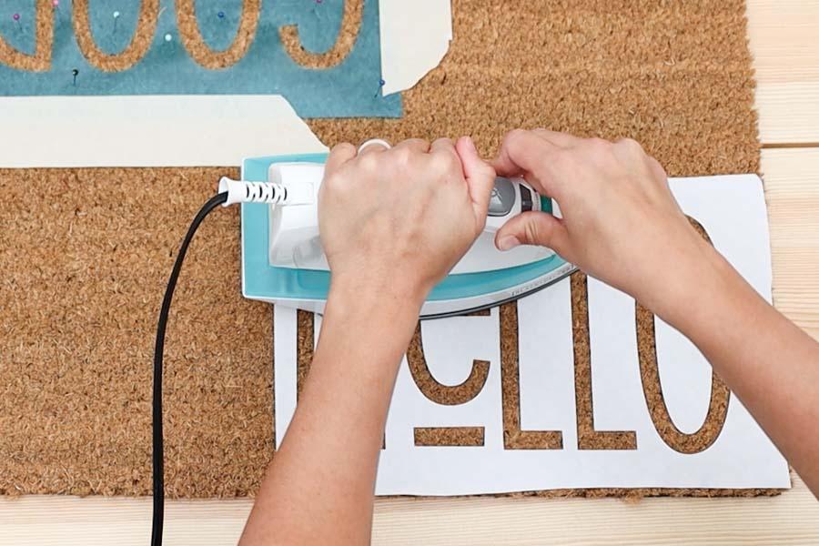 pressing freezer paper on doormat
