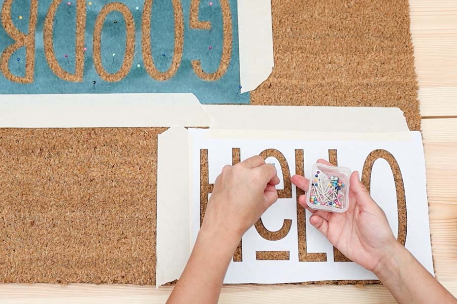 securing freezer paper stencil with sewing pins and masking tape